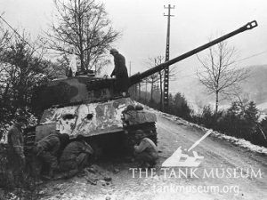 An abandoned Tiger II, with white flag flying, being inspected by American troops, in the Ardennes, France 1945.