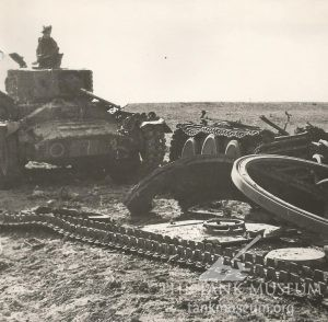 A Valentine of C Squadron 17th/21st Lancers which struck a mine while trying to work its way passed the Tiger. This photo was taken after the German tank was blown up to prevent it from being recovered by the enemy.