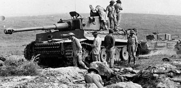Main_British troops pouring over a recently captured Tiger 131. A Churchill tank is seen in the background.